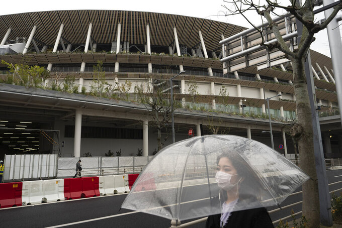 A woman walks past the New National Stadium, a venue for the opening and closing ceremonies at the Tokyo 2020 Olympics, in Tokyo, Monday, March 23, 2020. The IOC will take up to four weeks to consider postponing the Tokyo Olympics amid mounting criticism of its handling of the coronavirus crisis that now includes a call for delay from the leader of track and field, the biggest sport at the games. (AP Photo/Jae C. Hong)
