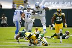 Detroit Lions' D'Andre Swift leaps over Green Bay Packers' Adrian Amos and Raven Greene during the second half of an NFL football game Sunday, Sept. 20, 2020, in Green Bay, Wis. (AP Photo/Mike Roemer)