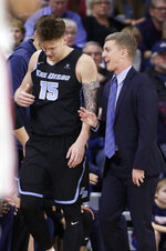San Diego head coach Sam Scholl, right, speaks with forward Alex Floresca (15) during the first half of an NCAA college basketball game against Gonzaga in Spokane, Wash., Saturday, Feb. 2, 2019. (AP Photo/Young Kwak)