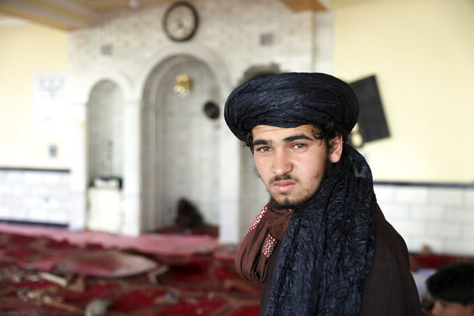 Religious student poses for photograph inside a mosque after a bomb explosion in Shakar Dara district of Kabul, Afghanistan, Friday, May 14, 2021. A bomb ripped through a mosque in northern Kabul during Friday prayers killing 12 worshippers, Afghan police said. (AP Photo/Rahmat Gul)
