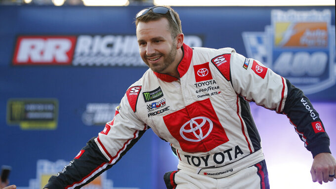 Matt DiBenedetto greets fans during driver introductions for the NASCAR Monster Energy Cup series auto race at Richmond Raceway in Richmond, Va., Saturday, Sept. 21, 2019. (AP Photo/Steve Helber)