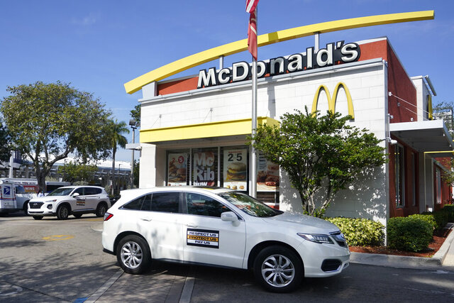A caravan of fast food workers circle a McDonald's restaurant as they demonstrate for higher wages, Friday, Jan. 15, 2021, in Fort Lauderdale, Fla. Workers in 15 cities demonstrated to demand $15/hr from corporations like McDonald's and to challenge President-elect Joe Biden's administration to raise the Federal Minimum Wage to $15/hr in his First 100 Days. (AP Photo/Wilfredo Lee)
