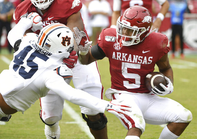 Arkansas running back Rakeem Boyd is tackled for a loss by Auburn defender Caleb Johnson during the second half of an NCAA college football game, Saturday, Oct. 19, 2019 in Fayetteville, Ark. (AP Photo/Michael Woods)