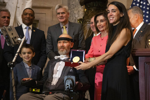 A Congressional Gold Medal is presented to amyotrophic lateral sclerosis (ALS) advocate and former National Football League (NFL) player, Steve Gleason, in Statuary Hall on Capitol Hill, Wednesday, Jan. 15, 2020, in Washington. Holding the medal is his wife Michel Gleason. (AP Photo/Manuel Balce Ceneta)