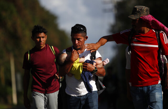 Honduran migrant Selvin Hernandez carries Mayra Irene, the baby daughter of another migrant, as another man tries to shade her with his hand amid a group of migrants trying to make it to the United States, near El Cinchado, Guatemala, Wednesday, Jan. 15, 2020, on the border with Honduras. (AP Photo/Moises Castillo)