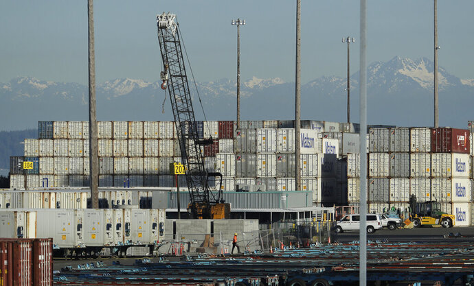 FILE - In this May 10, 2019 file photo, a worker walks near truck trailers and cargo containers at the Port of Tacoma in Tacoma, Wash. Hundreds of businesses, trade groups and individuals have written to complain about President Donald Trump's threat to impose tariffs on the remaining $300 billion in Chinese goods that he hasn't already hit with 25% import taxes, saying the additional import taxes would drive up prices for consumers, squeeze profits and leave U.S. companies at a competitive disadvantage to foreign rivals that aren't subject to higher taxes on the vital components they buy from China.  (AP Photo/Ted S. Warren, File)