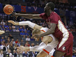 Florida State's Christ Koumadje, top, knocks the ball from Virginia's Jack Salt, bottom, during the first half of an NCAA college basketball game in the Atlantic Coast Conference tournament in Charlotte, N.C., Friday, March 15, 2019. (AP Photo/Nell Redmond)