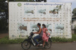 People wearing face masks to help curb the spread of the coronavirus ride a motorcycle past a Health Ministry public information campaign billboard about proper hand washing in Shwe Pyi Thar township in Yangon, Myanmar Wednesday, July 28, 2021. (AP Photo)