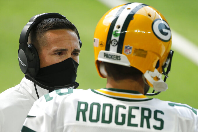 Green Bay Packers head coach Matt LaFleur, left, talks with quarterback Aaron Rodgers (12) during the first half of an NFL football game against the Minnesota Vikings, Sunday, Sept. 13, 2020, in Minneapolis. (AP Photo/Bruce Kluckhohn)