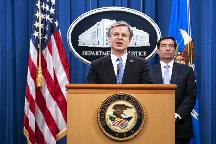FBI Director Christopher Wray speaks during a virtual news conference at the Department of Justice, Wednesday,  Oct. 28, 2020 in Washington, as Assistant Attorney General for National Security John Demers looks on. The Justice Department has charged eight people with working on behalf of the Chinese government to locate Chinese dissidents and political opponents living in the U.S. and coerce them into returning to China. Five of the eight were arrested Wednesday morning. (Sarah Silbiger/Pool via AP)