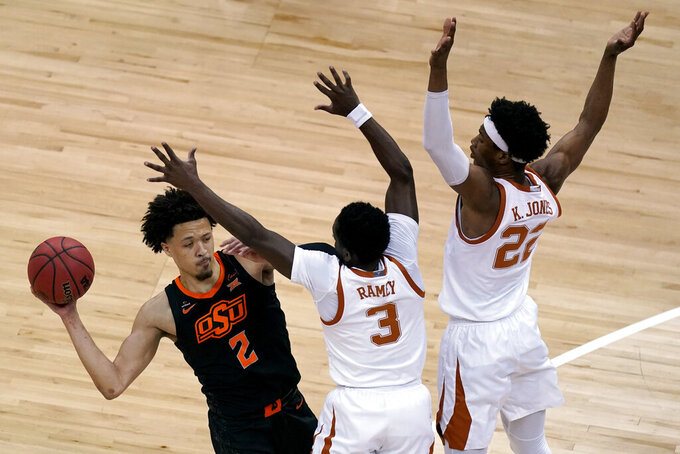 Oklahoma State's Cade Cunningham looks to pass under pressure from Texas's Kai Jones (22) and Courtney Ramey (3) during the first half of an NCAA college basketball game for the Big 12 tournament championship in Kansas City, Mo, Saturday, March 13, 2021. (AP Photo/Charlie Riedel)
