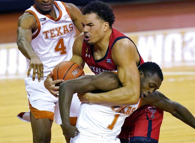 Texas Tech forward Marcus Santos-Silva, center, and Texas guard Andrew Jones (1) struggle for a rebound during the first half of an NCAA college basketball game Wednesday, Jan. 13, 2021, in Austin, Texas. (AP Photo/Eric Gay)