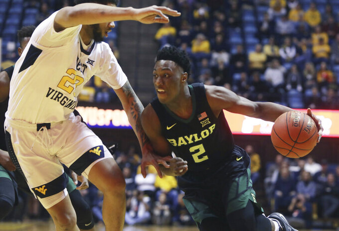 Baylor guard Devonte Bandoo (2) drives while defended by West Virginia forward Esa Ahmad (23) during the first half of an NCAA college basketball game Monday, Jan. 21, 2019, in Morgantown, W.Va. (AP Photo/Raymond Thompson)