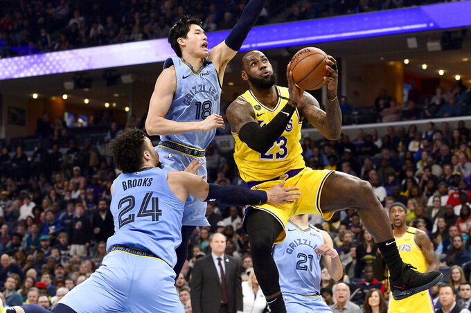 FILE - In this Feb. 29, 2020, file photo, Los Angeles Lakers forward LeBron James (23) shoots ahead of Memphis Grizzlies guards Yuta Watanabe (18) and Dillon Brooks (24) in the second half of an NBA basketball game in Memphis, Tenn. The Associated Press looks at some of the events that would have been live the week of April 20-26: The playoffs would be in full swing, with LeBron James and the Los Angeles Lakers in a possible first-round Western Conference matchup against the Memphis Grizzlies. (AP Photo/Brandon Dill, File)