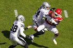 Las Vegas Raiders safety Johnathan Abram (24) and safety Jeff Heath (38) break up a pass intended for Kansas City Chiefs wide receiver Tyreek Hill (10) during the first half of an NFL football game, Sunday, Oct. 11, 2020, in Kansas City. (AP Photo/Charlie Riedel)