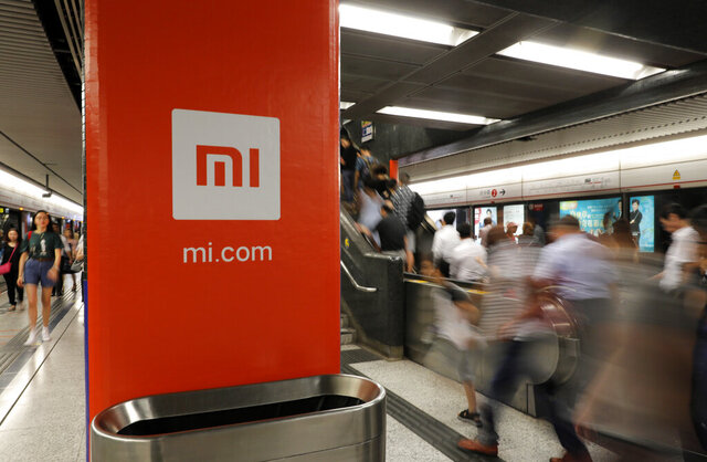 FILE - In this July 9, 2018, file photo, an advertisement for Xiaomi is displayed at a subway station in Hong Kong. The U.S. government has blacklisted Chinese smartphone maker Xiaomi Corp. and China's third-largest national oil company for alleged military links, heaping pressure on Beijing in President Donald Trump's last week in office. The Department of Defense added nine companies to its list of Chinese companies with military links, including Xiaomi and state-owned plane manufacturer Commercial Aircraft Corp. of China (Comac). (AP Photo/Vincent Yu, File)