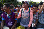 A Honduran migrant stands in line for breakfast at a temporary shelter in Tecun Uman, Guatemala in the border with Mexico, Sunday, Jan. 19, 2020. Mexican authorities have closed a border entry point in southern Mexico after thousands of Central American migrants tried to push across a bridge between Mexico and Guatemala. (AP Photo/Moises Castillo)