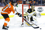 Philadelphia Flyers' Travis Konecny, left, passes the puck against Boston Bruins' Tuukka Rask during the second period of an NHL hockey game, Tuesday, March 10, 2020, in Philadelphia. (AP Photo/Matt Slocum)
