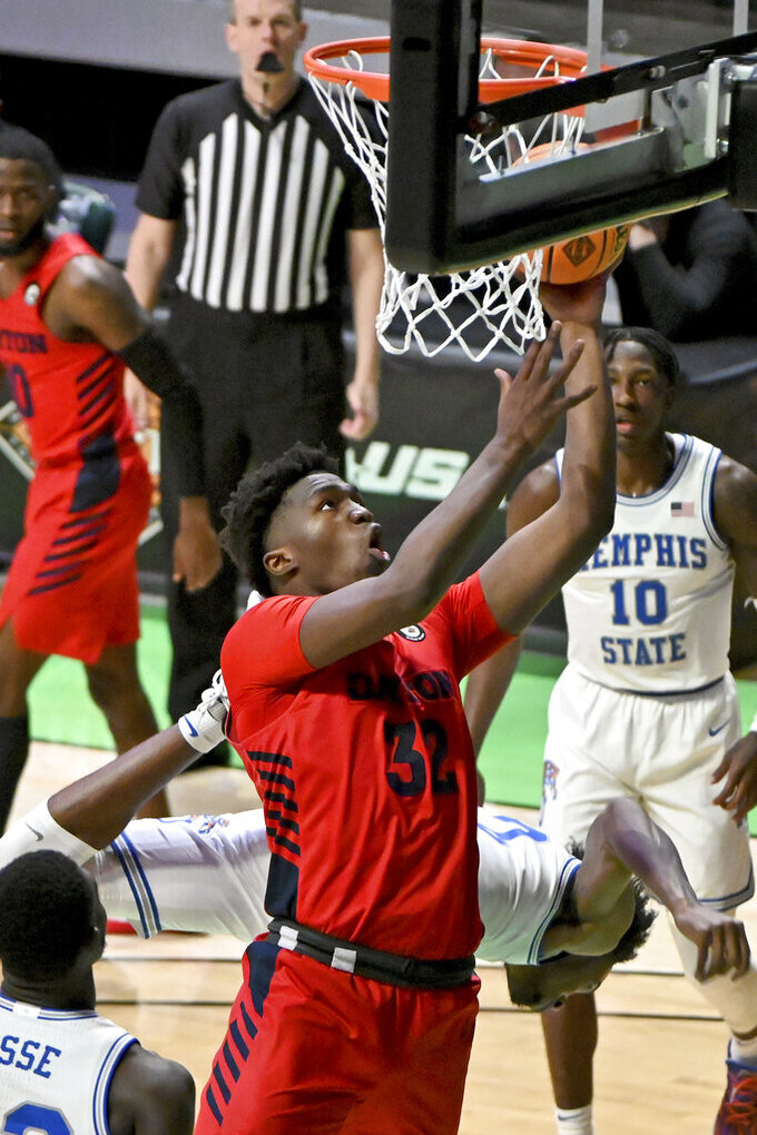 Dayton center Jordy Tshimanga (32) goes up for a shot after being fouled by Memphis forward DeAndre Williams (12) in the first half of an NCAA college basketball game in the first round of the NIT Tournament, Saturday, March 20, 2021, in Denton, Texas. (AP Photo/Matt Strasen)