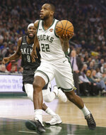 Milwaukee Bucks' Khris Middleton, right, drives against Brooklyn Nets' DeMarre Carroll, left, during the first half of an NBA basketball game Saturday, April 6, 2019, in Milwaukee. (AP Photo/Jeffrey Phelps)