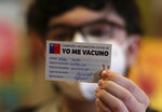 Edu Soto, 15, shows his vaccination card to the camera after getting a first dose of the Pfizer vaccine for COVID-19 at the Teleton Institute, a clinic that specializes in treating chronically ill children in Santiago, Chile, Tuesday, June 22, 2021, on the first day the government started vaccinating youths between ages 12 and 17 who have chronic illnesses. (AP Photo/Esteban Felix)