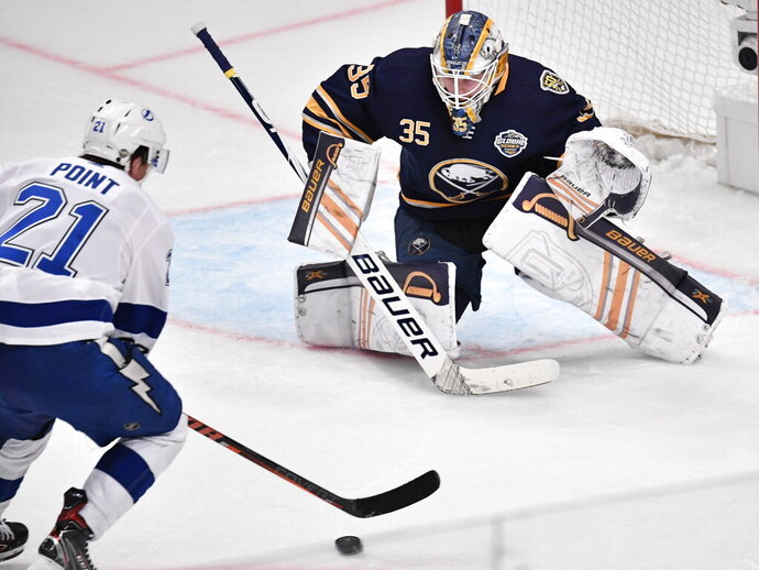 Tampa Bay Lightning Brayden Point (21) take a shot as Buffalo Sabres' goalie Linus Ullman defends during an NHL hockey game in Globen Arena, Stockholm Sweden. Friday. Nov. 8, 2019. (Anders Wiklund/TT via AP)