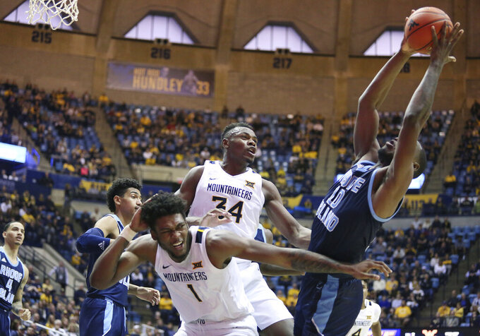Rhode Island forward Cyril Langevine (10) catches a rebound off the net as he is defended by West Virginia forward Derek Culver (1) and West Virginia forward Oscar Tshiebwe (34) during the second half of an NCAA college basketball game Sunday, Dec. 1, 2019, in Morgantown, W.Va. (AP Photo/Kathleen Batten)