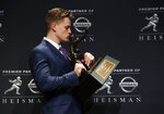 NCAA college football player, LSU quarterback Joe Burrow poses for a photo after winning the Heisman Trophy, Saturday, Dec. 14, 2019, in New York. (AP Photo/Jason Szenes)