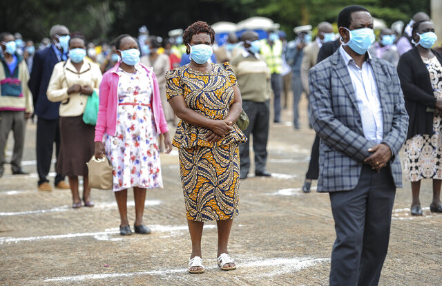 County workers practise social distancing and wear masks as they queue to renew their employment contracts in Uhuru Park in downtown Nairobi, Kenya Monday, April 6, 2020. Kenya on Monday increased its restrictions to combat the new coronavirus, announcing travel bans into and out of the capital city, Nairobi, the port of Mombasa and two counties. (AP Photo/John Muchucha)