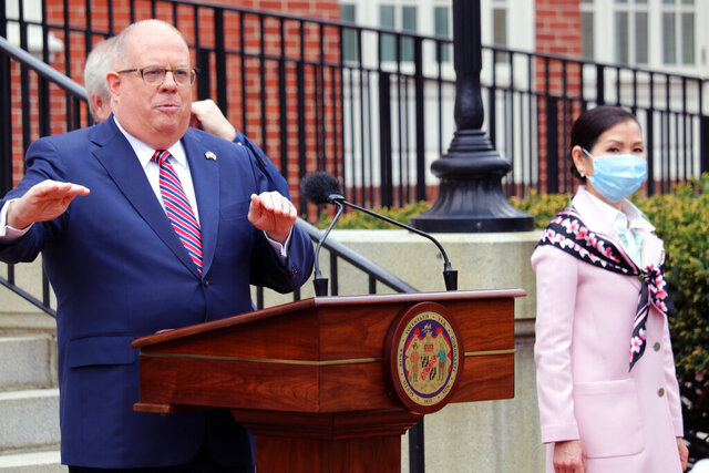 FILE - In this Monday, April 20, 2020  file photo, Maryland Gov. Larry Hogan speaks at a news conference in Annapolis, Md., with his wife, Yumi Hogan, right, where the governor announced Maryland has received a shipment from a South Korean company to boost the state's ability to conduct tests for COVID-19 by 500,000. Maryland lawmakers are renewing criticism of Gov. Larry Hogan's procurement of 500,000 COVID-19 tests from South Korea after The Washington Post reported the first batch was flawed and never used, Friday, Nov. 20, 2020. (AP Photo/Brian Witte, File)