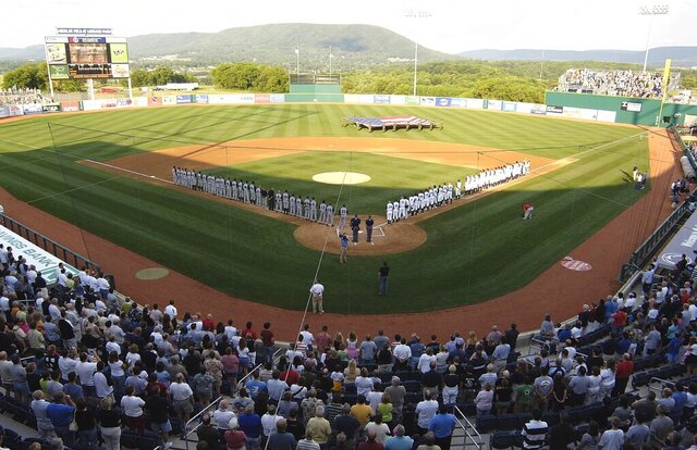 FILE - In this June 20, 2006, file photo, teams line up along the baselines during the playing of the national anthem before the first game, in the inaugural season, of the State College Spike baseball team in State College, Pa. Major League Baseball is creating a minor league for top eligible prospects leading to the summer draft., the league announced Monday, Nov. 30, 2020. The founding members of the MLB Draft League are located in Ohio, Pennsylvania, West Virginia and New Jersey: the Mahoning Valley Scrappers, the State College Spikes, the Trenton Thunder, the West Virginia Black Bears and the Williamsport Crosscutters. (AP Photo/Pat Little, File)