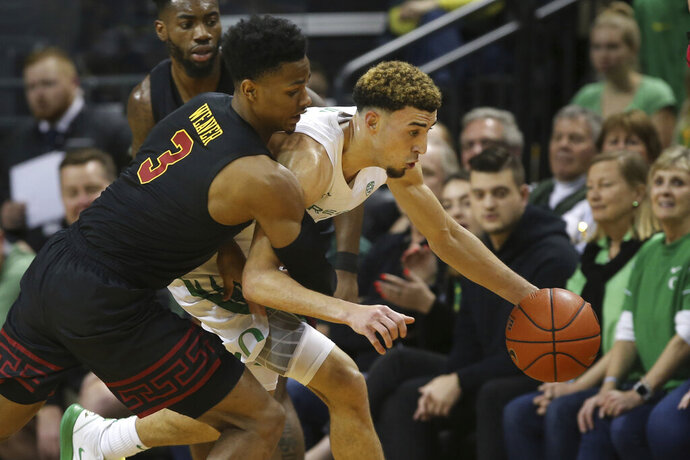 Oregon's Chris Duarte, right, steals the ball from Southern California's Daniel Utomi, back, and Elijah Weaver during the first half of an NCAA basketball game in Eugene, Ore., Thursday, Jan. 23, 2020. (AP Photo/Chris Pietsch)