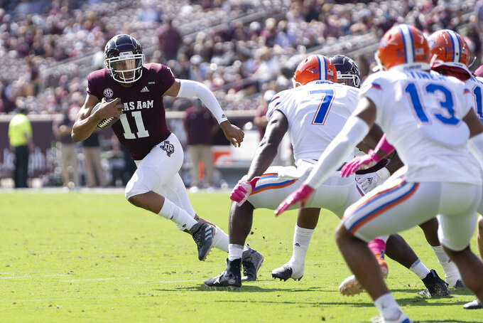 Texas A&M quarterback Kellen Mond (11) looks to run against Florida linebacker Jeremiah Moon (7) during the first quarter of an NCAA college football game, Saturday, Oct. 10, 2020. in College Station, Texas. (AP Photo/Sam Craft)