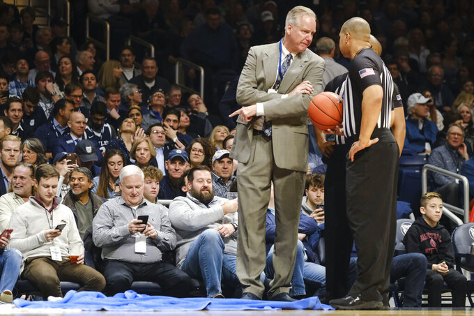 Butler athletic director Barry Collier talks with officials while pointing at a set of towels soaking up water from a roof leak that caused a delay in play in the first half of an NCAA college basketball game between Villanova and Butler in Indianapolis, Wednesday, Feb. 5, 2020. (AP Photo/AJ Mast)