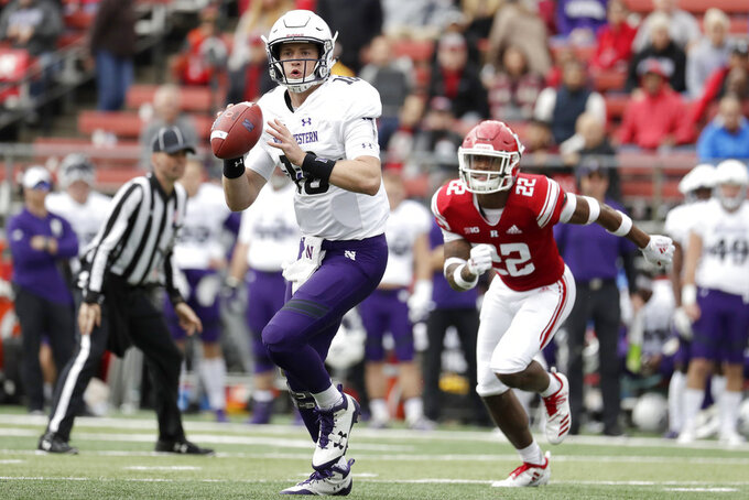 Northwestern quarterback Clayton Thorson (18) looks to pass as Rutgers defensive back Damon Hayes (22) tries to stop him during the first half of an NCAA college football game, Saturday, Oct. 20, 2018, in Piscataway, N.J. (AP Photo/Julio Cortez)