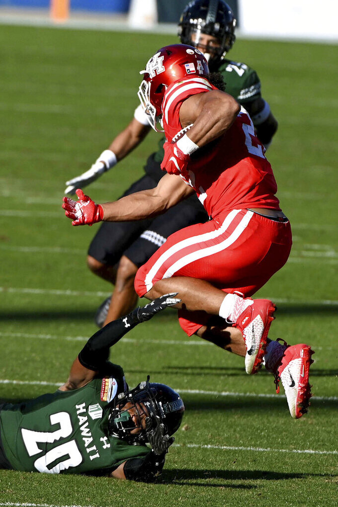 Houston running back Kyle Porter (22) leaps over a tackle attempt by Hawaii defensive back Cameron Lockridge (20) in the second quarter of the New Mexico Bowl NCAA college football game in Frisco, Texas, Thursday, Dec. 24, 2020. (AP Photo/Matt Strasen)