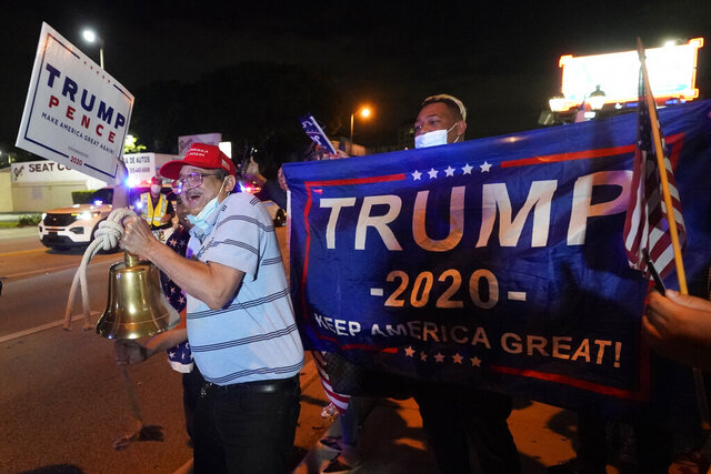 In this Nov. 3, 2020, photo, Rafael Fagundo rings a bell as he and other supporters of President Donald Trump chant and wave flags outside the Versailles Cuban restaurant during a celebration on election night in the Little Havana neighborhood of Miami. As election postmortems go, the one that began in Florida Wednesday was especially wrenching for Democrats. While they could share in the possibility of a Biden victory, as other battleground states continue to tally votes, the soul searching and second-guessing has begun amid another high-profile loss at the ballot box. (AP Photo/Wilfredo Lee)