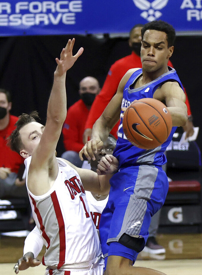 Air Force forward Nikc Jackson (22) passes as UNLV forward Moses Wood (1) defends during the first half of an NCAA college basketball game in the first round of the Mountain West Conference men's tournament Wednesday, March 10, 2021, in Las Vegas. (AP Photo/Isaac Brekken)