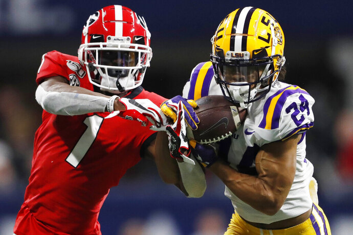 FILE - In this Dec. 7, 2019, file photo, LSU cornerback Derek Stingley Jr. (24) intercepts the ball from Georgia wide receiver George Pickens (1) during the second half of the Southeastern Conference championship NCAA college football game, in Atlanta.   LSU says Stingley Jr. has been ruled out of the No. 6 Tigers' opener Saturday, Sept. 26, 2020 against Mississippi State because of an illness. LSU spokesman Michael Bonnette says Stingley's illness is not COVID-19 and that the sophomore is expected to rejoin football activities after concluding medical treatment evaluation by doctors.  (AP Photo/John Bazemore, File)