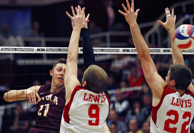 FILE - Loyola Chicago's Jeff Jendryk, left, hits past Lewis University's Greg Petty (9) and Jacob Schmiegelt (22) during the NCAA men's volleyball championship match, in Stanford, Calif., in this Saturday, May 9, 2015, file photo. Brad Hurlbut took over as the athletic director at Fairleigh Dickinson in 2019,  planning to increase the number of sports played at the small Division I school a short ride from New York City. In a little over two years, Hurlbut has taken his first step, announcing last month that men's volleyball will be added in 2021-22 and women's lacrosse would follow the next year. (AP Photo/George Nikitin)