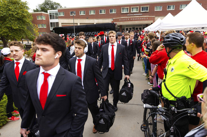 """The Nebraska football team arrives for a """"Unity Walk"""" among fans on campus from Selleck Quadrangle to Memorial Stadium before playing Northwestern in an NCAA college football game, Saturday, Oct. 2, 2021, in Lincoln, Neb. (AP Photo/Rebecca S. Gratz)"""