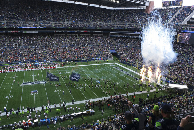 Fire effects go off as Seattle Seahawks players run out of the tunnel at the start of their home opener NFL football game against the Cincinnati Bengals at CenturyLink Field, Sunday, Sept. 8, 2019, in Seattle. (AP Photo/Stephen Brashear)