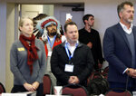 In this Oct. 17, 2018 photo, Jesse Nightwalker, second from left, of Tacoma, Wash., a member of the Palouse tribe, wears a ceremonial headdress as he takes video during a meeting of the Southern Resident Killer Whale Recovery Task Force in Tacoma. Nightwalker said he is in support of calls to breach four hydroelectric dams in Washington state as the plight of the critically endangered Northwest orca whales has captured global attention. (AP Photo/Ted S. Warren)