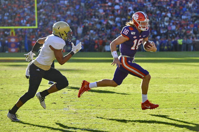 Clemson quarterback Trevor Lawrence (16) runs on a quarterback-keeper for a touchdown while defended by Wofford's Keyvaun Cobb during the first half of an NCAA college football game, Saturday, Nov. 2, 2019, in Clemson, S.C. (AP Photo/Richard Shiro)