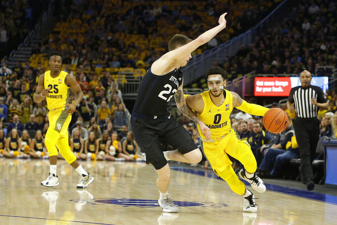 Marquette's Markus Howard (0) drives to the basket against Butler's Sean McDermott (22) during the first half of an NCAA college basketball game Sunday, Feb. 9, 2020, in Milwaukee. (AP Photo/Aaron Gash)
