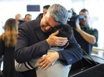 Ryan Pourjam, 13, son of Mansour Pourjam, is embraced by family friend Mahmoud Rastgou, after a ceremony  Wednesday, Jan. 15, 2020 at Carleton University to honour Pourjam, a biology alumnus, and biology PhD student Fareed Arasteh, who died in the crash of Ukraine International Airlines Flight PS752 in Tehran.  (Justin Tang/The Canadian Press via AP)