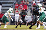 North Carolina State offensive tackle Ikem Ekwonu (79) blocks while running back Zonovan Knight (7) runs the ball as South Florida linebacker Andrew Mims (59) looks to tackle at left during the first half of an NCAA college football game in Raleigh, N.C., Thursday, Sept. 2, 2021. (AP Photo/Gerry Broome)