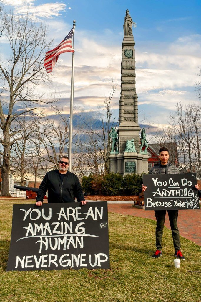 In this April 8, 2018 photo, Greg Amaral, left, and Wendell Walker, right, stand with signs showing positive messages in front of the Soldiers and Sailors Monument on Main Street, in Nashua, N.H.  The two have showed up on with feel-good signs each weekend since Easter Sunday. They say their goal is to encourage people to be happy and follow their dreams. (Craig Michaud via AP)