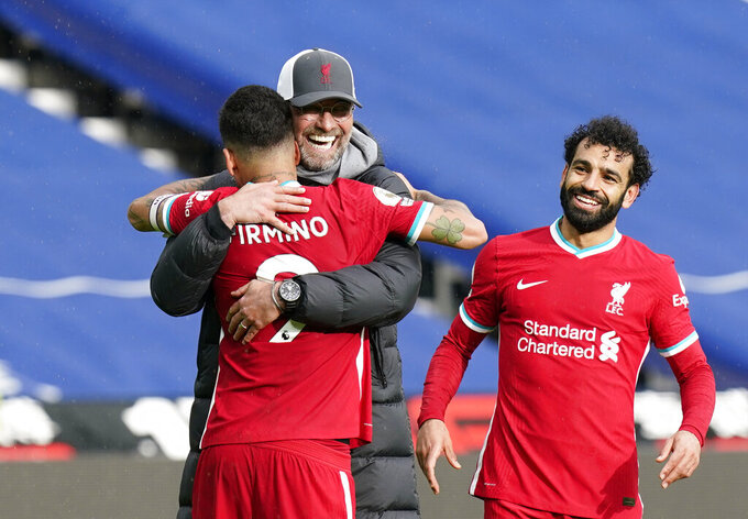 Liverpool's manager Jurgen Klopp, center, celebrates with Liverpool's Roberto Firmino, front, and Liverpool's Mohamed Salah at the end of the English Premier League soccer match between West Bromwich Albion and Liverpool at the Hawthorns stadium in West Bromwich, England, Sunday, May 16, 2021. (Tim Keeton/Pool via AP)