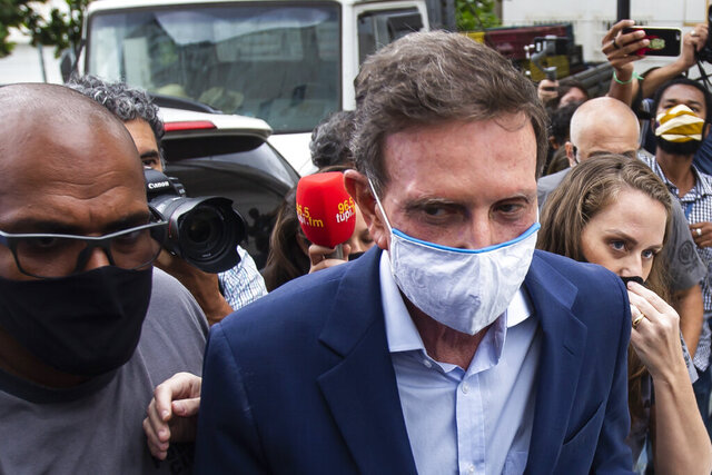 Rio de Janeiro Mayor Marcelo Crivella is escorted to a medical exam after his arrest, at the city police headquarters in Rio de Janeiro, Brazil, Tuesday, Dec. 22, 2020. Rio de Janeiro state police arrested the outgoing mayor on Tuesday in connection with an alleged kickbacks scheme. (AP Photo/Bruna Prado)